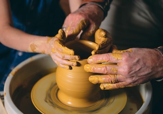 Taller de alfarería. el abuelo le enseña cerámica a su nieta. modelado de arcilla