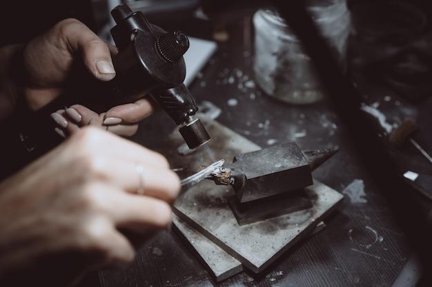 En el taller, una mujer joyero está ocupada soldando joyas