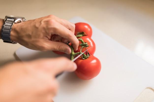 Tallo de corte de mano del hombre de tomates rojos con cuchillo afilado