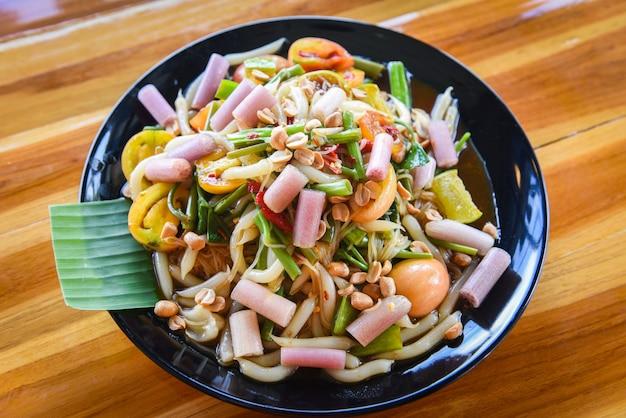Tallo de loto con ensalada de papaya, mezcla de fideos vegetales y maní servido en la mesa de comedor, fideos de arroz