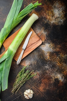 Tallos de puerro orgánicos con ingredientes de hierbas para cocinar puerros estofados, fondo de metal rústico oscuro, vista superior con espacio para texto.