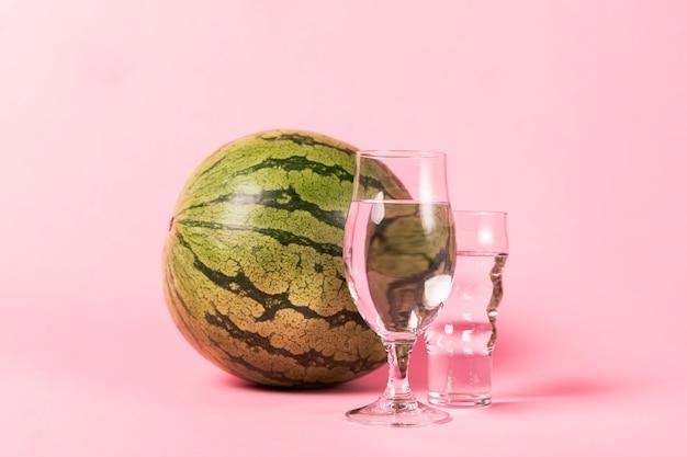 Tamaño completo de sandía y vasos con agua