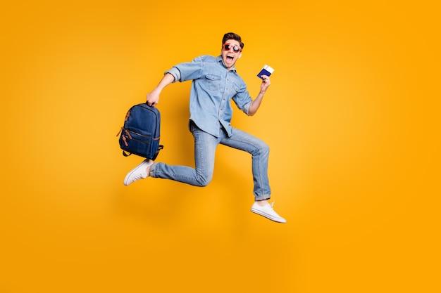 Tamaño de cuerpo entero convertido en foto de hombre gritando corriendo saltando hacia el aeropuerto con zapatos blancos y cartera en manos aisladas pared de color amarillo vivo