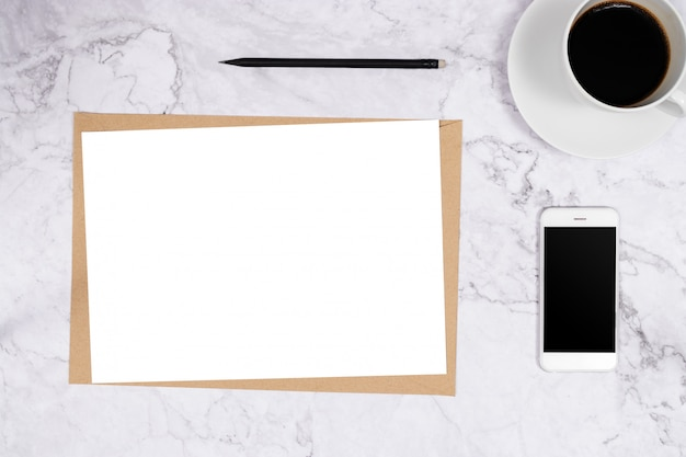 Tamaño de papel blanco a4 en blanco sobre papel marrón sobre mármol blanco
