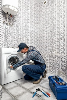 Tambor seco es buen fontanero hombre comprobando el trabajo de la lavadora