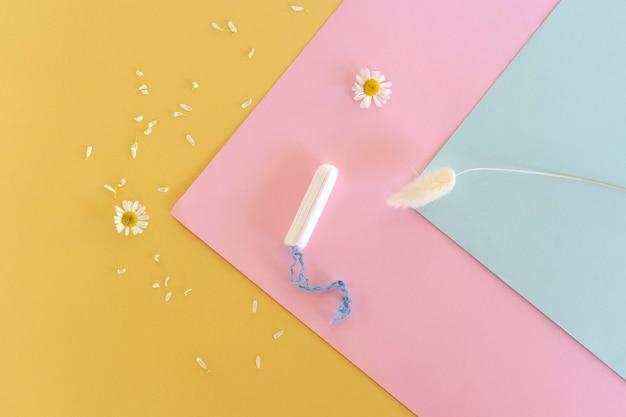 Un tampón sanitario se encuentra sobre un fondo de colores. días de menstruación. concepto de higiene y frescura
