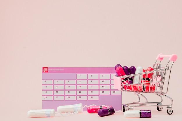 Tampones en un carrito de compras y un calendario.