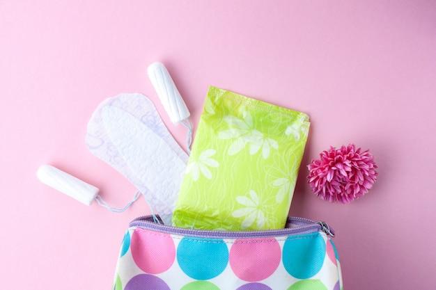 Tampones, toallas sanitarias femeninas, flores y bolsa de cosméticos para mujer. cuidado de la higiene durante los días críticos. ciclo menstrual. cuidar la salud de la mujer.