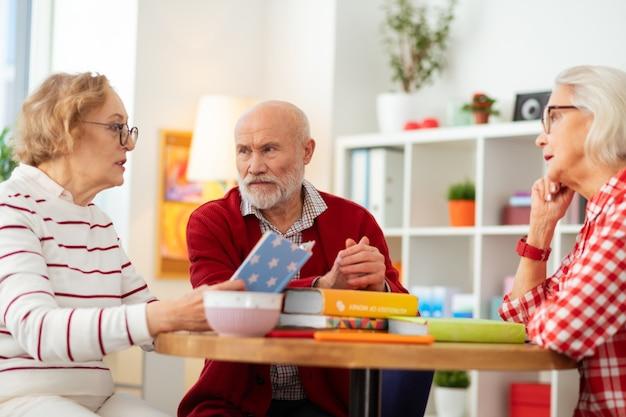 Tan atractivo. agradables personas mayores sentadas alrededor de la mesa mientras escuchan a su amigo