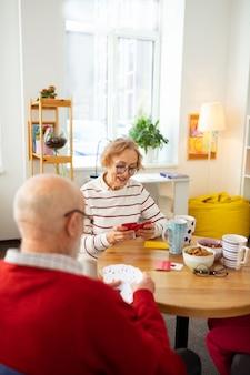 Tan atractivo. ancianos agradables sonriendo mientras juegan juegos de cartas juntos