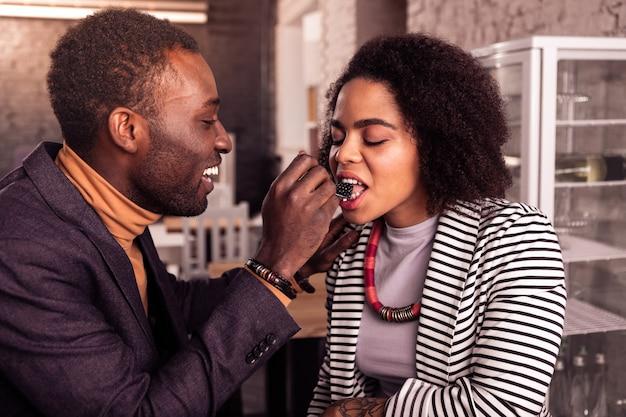 Tan delicioso. bonita mujer afroamericana cerrando los ojos mientras come una mora