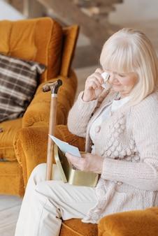 Tan emocional. anciana infeliz deprimida sosteniendo un pañuelo de papel y llorando mientras da vuelta cartas viejas