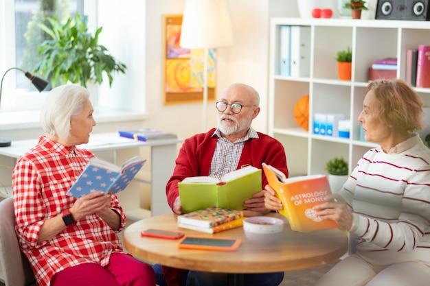 Tan emocionante. ancianos agradables sentados alrededor de la mesa mientras hablan sobre sus libros