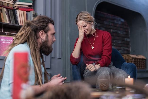 Tan estresado. mujer triste deprimida sosteniendo su frente mientras habla con el adivino
