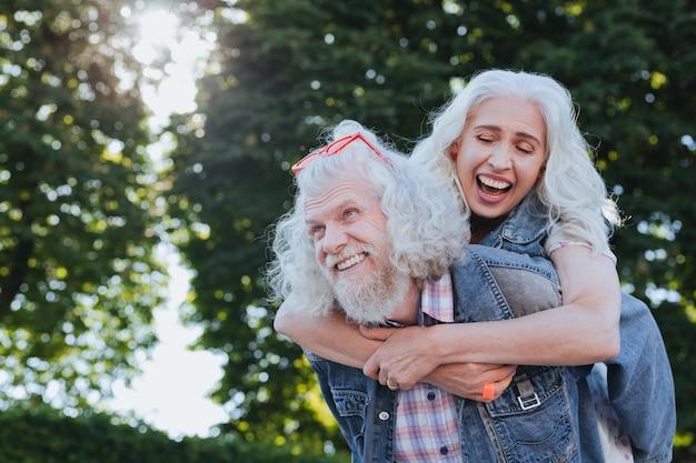 Tan feliz. bonita mujer alegre sonriendo mientras está junto con su marido