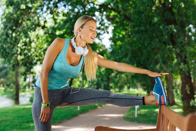 Tan flexible. encantado de mujer bonita mirando su pierna mientras hace ejercicio de flexibilidad