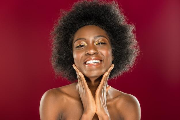 Tan hermoso. encantado de mujer bonita sonriendo mientras está de pie contra la pared roja