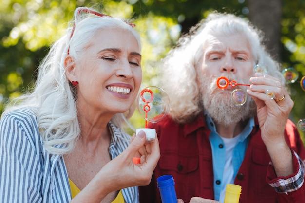 Tan hermoso. mujer de edad encantada mirando la burbuja de jabón mientras se divierte junto con su marido