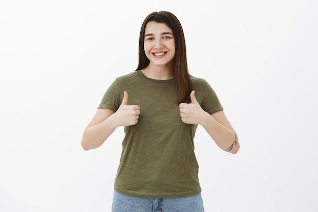 Tan impresionante, como tu idea. retrato de alegre y complacida linda chica de los años 20 con tatuaje sonriendo encantada y alegre mostrando los pulgares hacia arriba en gesto de aprobación y apoyo, reaccionando a una excelente sugerencia