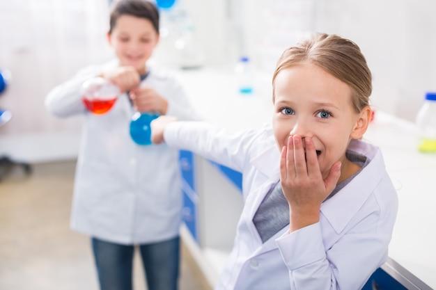 Tan interesante. bonita chica emocionada positiva mirándote y tapándose la boca mientras realiza un experimento con su amiga