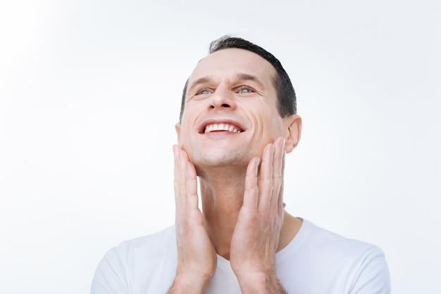 Tan suave. feliz buen hombre positivo sonriendo y tocando sus mejillas mientras está de pie contra el fondo blanco.