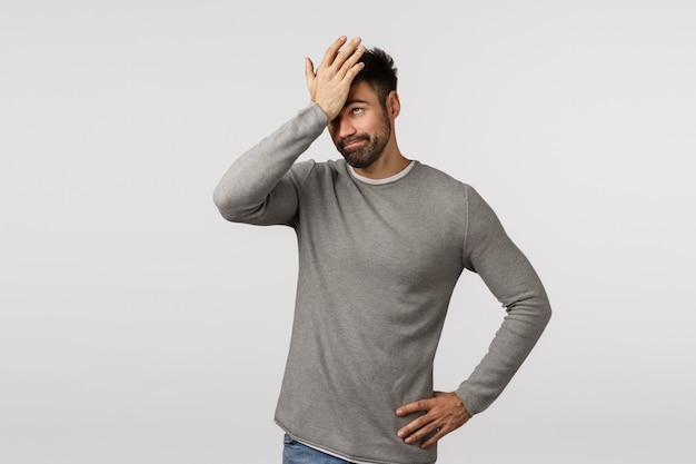 Tan tonto. olvidado y disgustado, hombre barbudo cansado con suéter gris, palmada en la cara, golpear la frente como se olvidó de una tarea importante, escuchar una tonta idea estúpida, sonreír molesto, de pie avergonzado