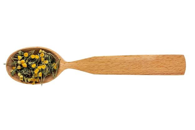 Tanacetum seco en una cuchara de madera sobre un fondo blanco.