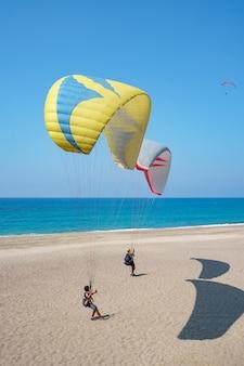 Tándem de parapente volando sobre la orilla del mar con agua azul y cielo en horison. vista del parapente y la laguna azul en turquía.