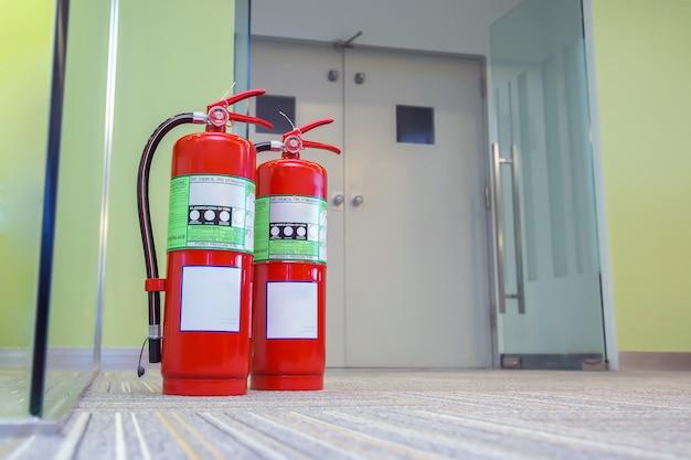 Tanque de extintores rojos en la puerta de salida del edificio