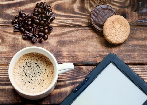 Tapa de café con espuma, ebook, pasteles, granos de café en forma de corazón sobre la mesa de madera
