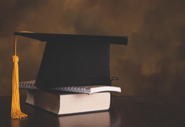 Tapa de graduación en paso de libros en la sala de la biblioteca del campus y la universidad, concepto de educación internacional en el extranjero, regreso a la escuela