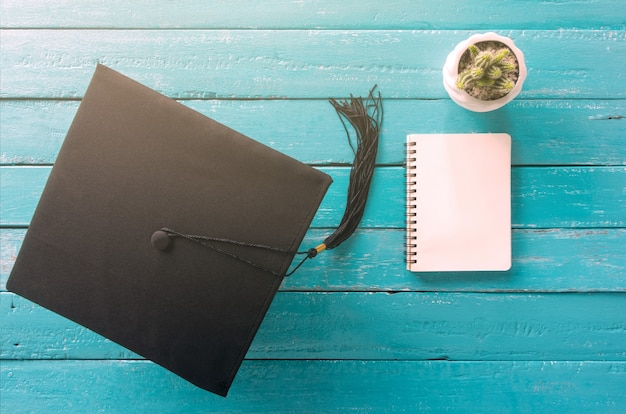 Tapa de graduación, sombrero en mesa de madera azul con vista de cuaderno vacío desde arriba.