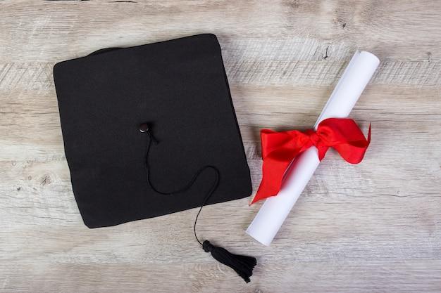 Tapa de graduación, sombrero con papel de grado en concepto de graduación de mesa de madera