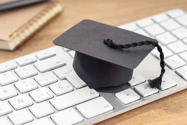 Tapa de graduación en el teclado de la computadora en un escritorio de madera