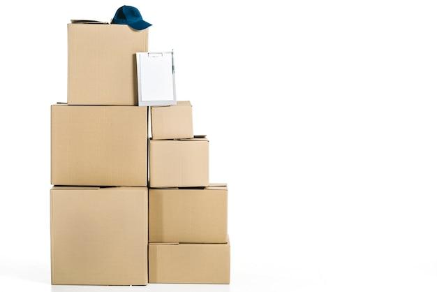 Tapa y portapapeles en pila de cajas