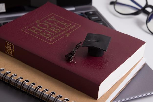 Tapa de posgrado en las páginas de la santa biblia.