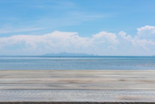 Tapa de tabla de madera del tablón con el fondo azul borroso del cielo del mar