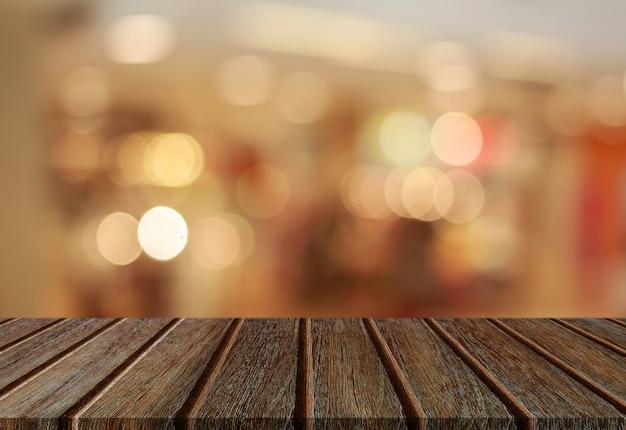 Tapa de tabla vacía del tablón de madera de la perspectiva con el fondo ligero abstracto del bokeh