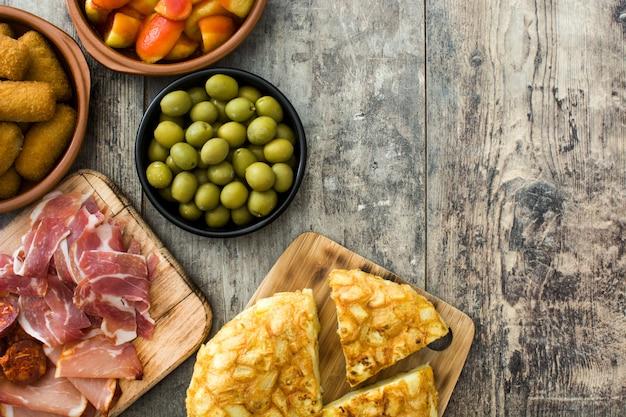 Tapas españolas tradicionales. croquetas, aceitunas, tortilla, jamón y patatas bravas en mesa de madera copia espacio