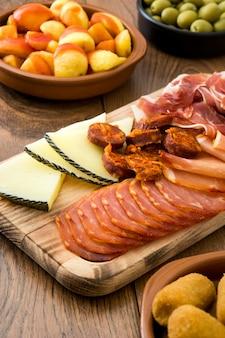 Tapas españolas tradicionales. croquetas, aceitunas, tortilla, jamón y patatas bravas en mesa de madera
