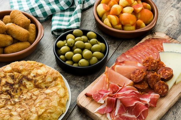 Tapas españolas tradicionales croquetas, aceitunas, tortilla, jamón y patatas bravas en mesa de madera