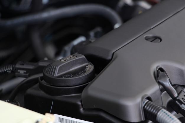 Tapón de aceite de motor o aceite de motor debajo del capó de un automóvil. mantenimiento de automóviles o reparación de concepto automotriz.