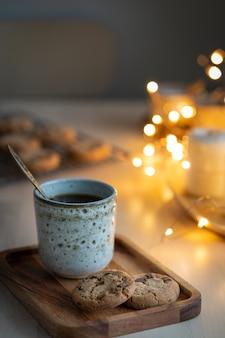 Tarde acogedora, taza de bebida, adornos navideños, velas y guirnaldas de luces.