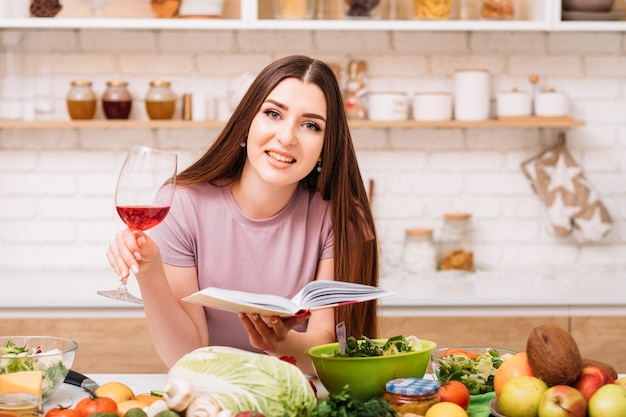 Tarde en casa. pasatiempo de cocina. mujer joven sonriente con copa de vino tinto. libro de recetas saludables en manos.