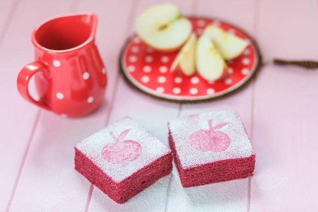 Tarde de té, manzanas frescas, pastel de pastila de grosella cuadrada.