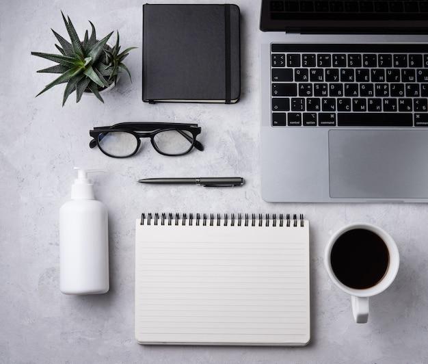 Tarea. business flat lay con desinfectante, nota, lápiz, anteojos, cuaderno y cuculento, sobre fondo blanco beton