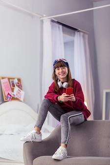 Tarea creativa. encantadora niña sentada en el sofá y escribiendo mensaje