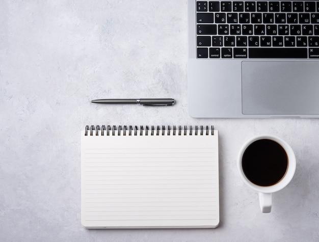Tarea. negocio plano pone con taza de café, nota, lápiz sobre fondo blanco beton