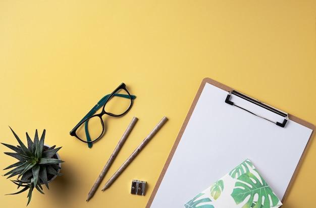 Tarea. negocio plano yacía con nota, lápiz, gafas y suculenta sobre fondo amarillo.