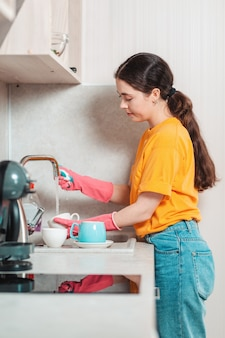 Tareas del hogar. una mujer bonita con ropa casual y guantes de goma rosa está lavando platos. vista lateral